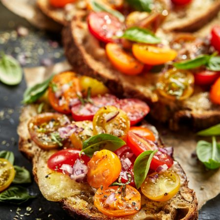 Tomato bruschetta with grilled homemade bread with cheese and fresh herbs